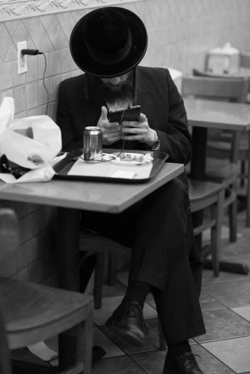 Satmar man using Tablet at restaurant in Williamsburg. Photo Credit: Mark Hanover
