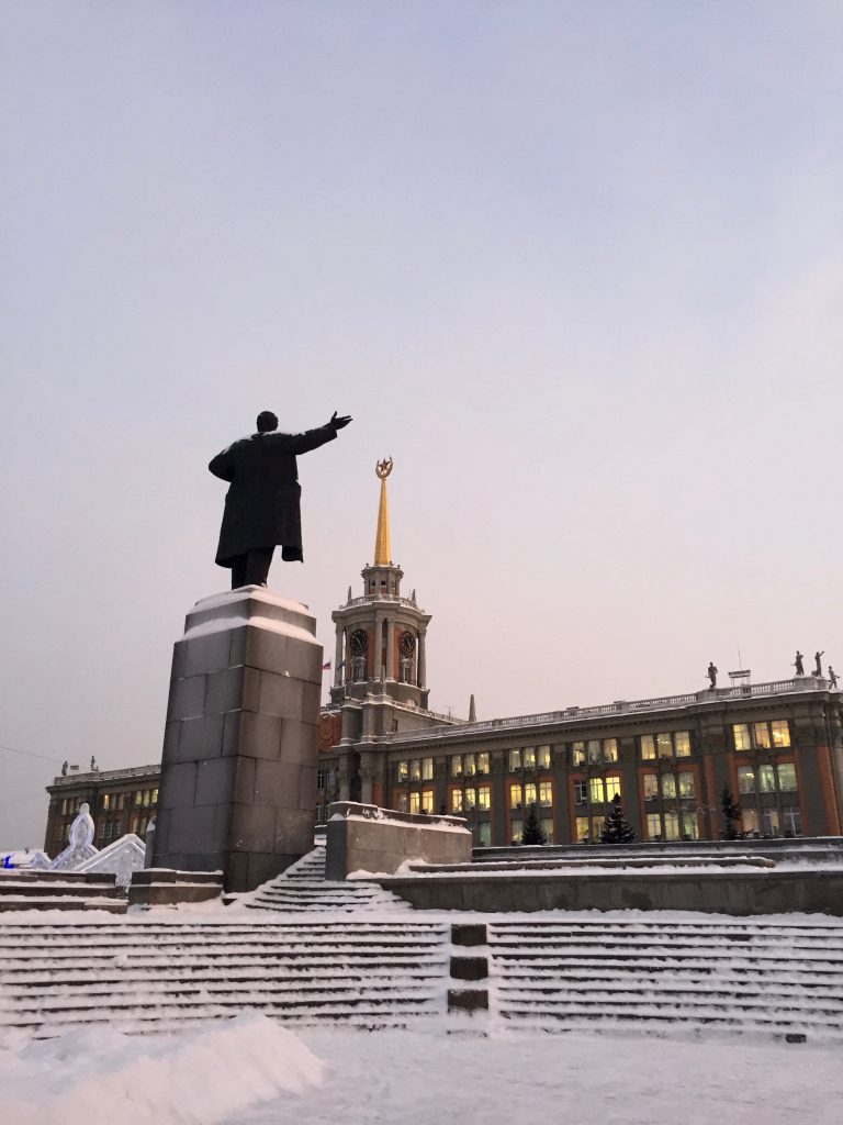 A statue of Lenin stands opposite of Yekaterinburg's city administration building that is topped with a red Soviet star.